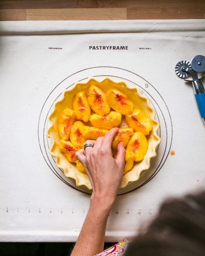 Placing peaches in a pie crust