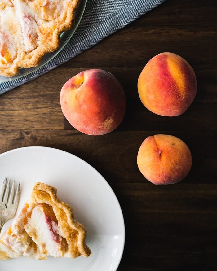 slice of homemade peach pie on white plate next to fresh peaches