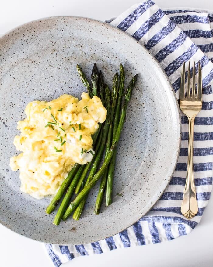 Fluffy scrambled eggs on a plate with asparagus