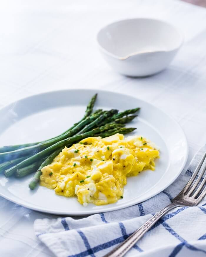 Fluffy scrambled eggs with asparagus on a plate
