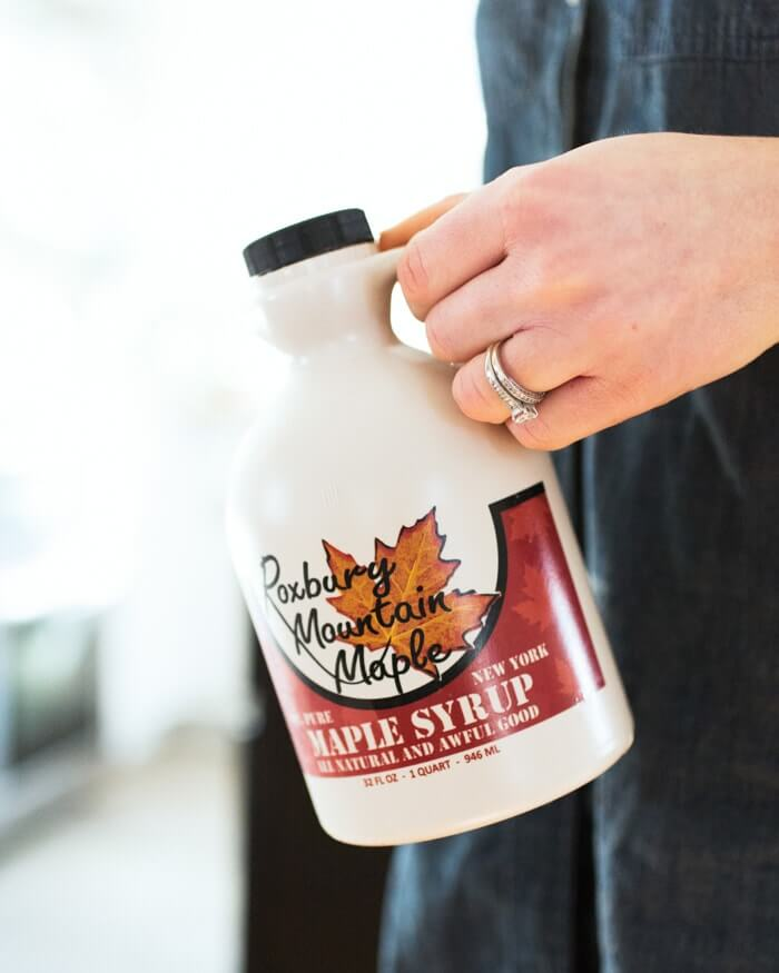 holding a bottle of maple syrup