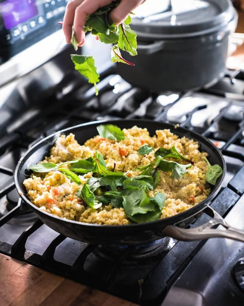 Greens going into pan on stove