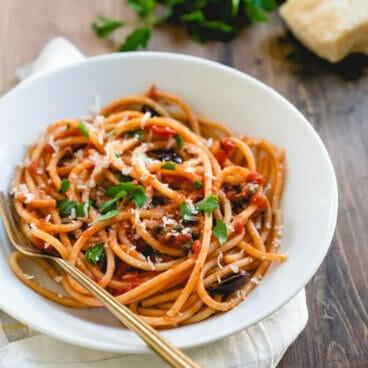 homemade pasta puttanesca in white bowl