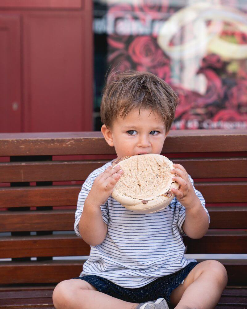 Traveling with a Toddler   Travel bed, packing list   Boy with pastry in Spain
