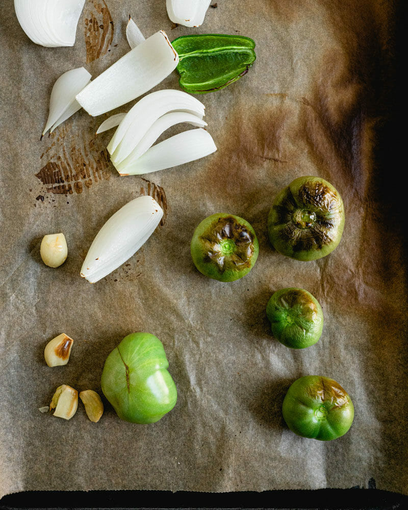 Green tomatoes and onion on baking sheet