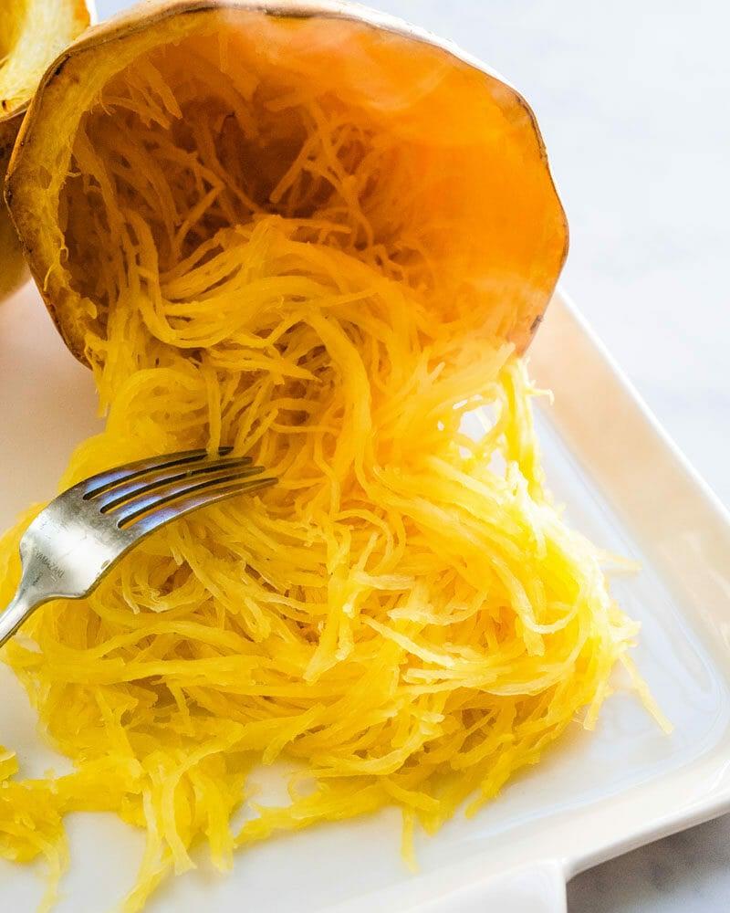 Scraping the spaghetti squash into strands